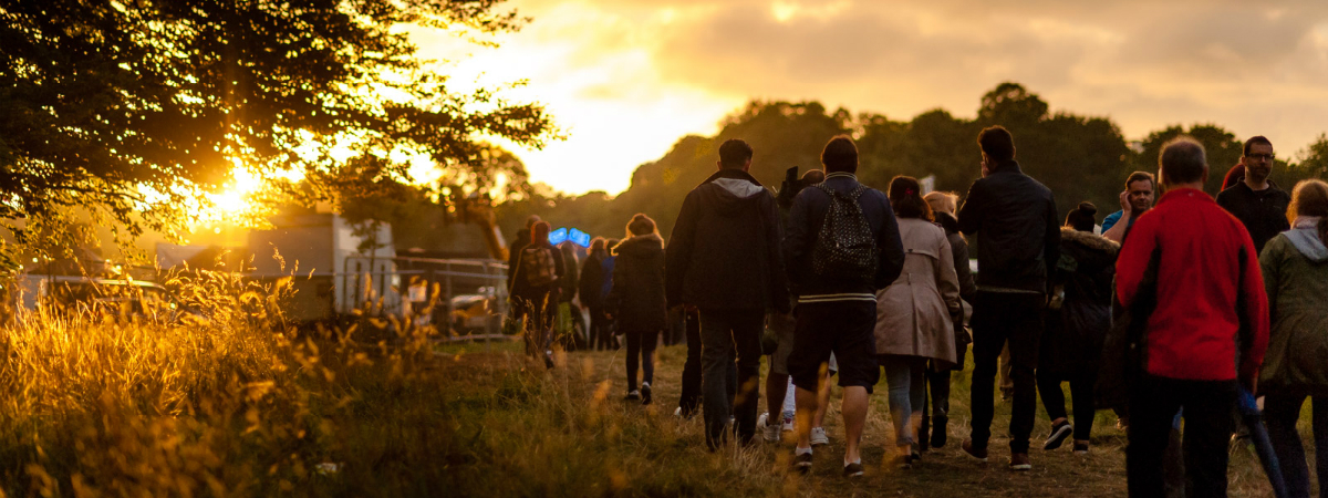 People heading to LIMF, walking across a field surrounded by trees as the sun sets in the sky