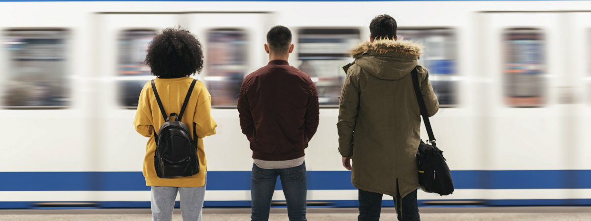 Three people on a platform waiting to travel by train